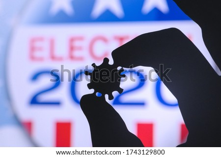 Hand silhouette hold covid 19 virus. Logo of USA presidental Election 2020 in background. US presidential elections are threatened by coronavirus and may be postponed #1743129800