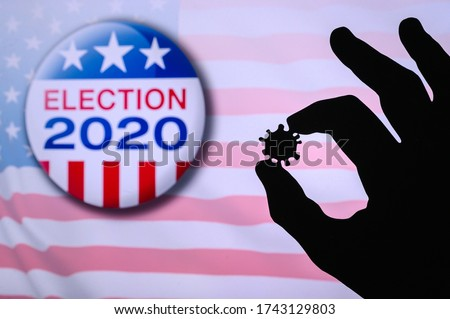 Hand silhouette hold covid 19 virus. Logo of USA presidental Election 2020 in background. US presidential elections are threatened by coronavirus and may be postponed #1743129803