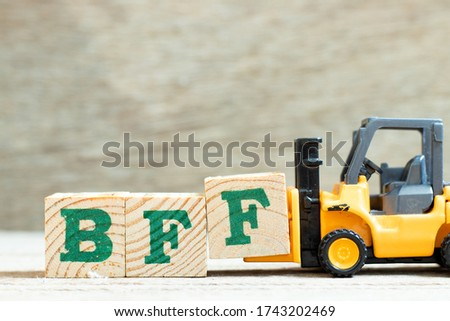 Toy forklift hold letter block f to complete word BFF (Abbreviation of best friend forever) on wood background #1743202469