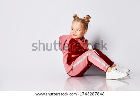 Little blonde girl with buns hairstyle, in colorful tracksuit, sneakers. She laughing, sitting on floor, posing isolated on white. Childhood, fashion, advertising and sport. Close up, copy space Royalty-Free Stock Photo #1743287846