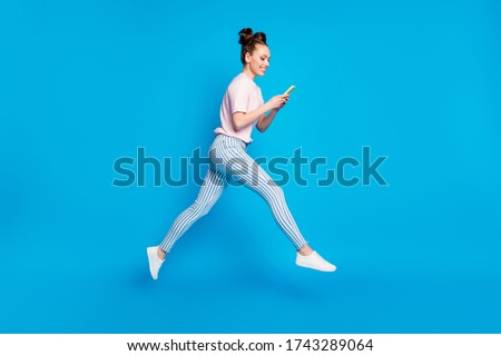 Full length body size view of her she nice attractive pretty focused cheerful cheery girl jumping using cell app 5g blogging chatting isolated on bright vivid shine vibrant blue color background