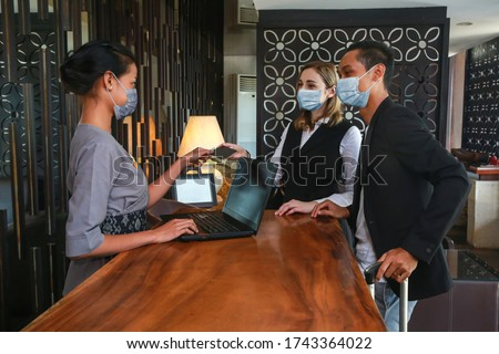Couple and receptionist at counter in hotel wearing medical masks as precaution against virus. Young couple on a business trip doing check-in at the hotel Royalty-Free Stock Photo #1743364022