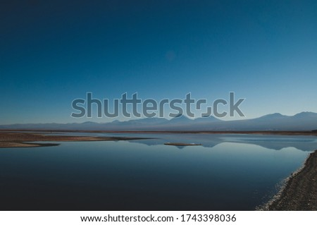 Quietly situated sea with a view of distant mountains on the horizon Royalty-Free Stock Photo #1743398036