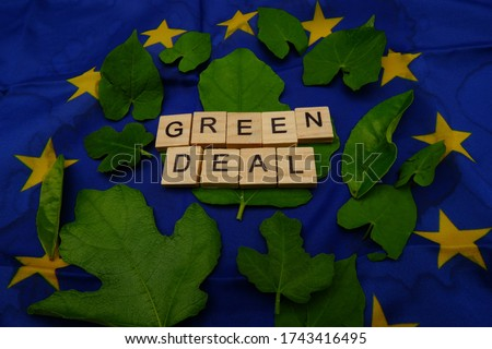 Some leaves,with a wooden inscription,green deal,above a European flag. Concept of fighting climate change on earth  Royalty-Free Stock Photo #1743416495