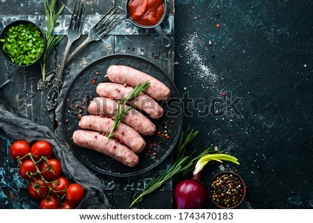 Raw barbecue sausages with spices and vegetables. Top view. Free space for your text. Royalty-Free Stock Photo #1743470183
