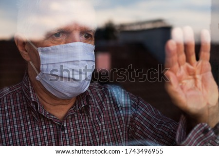 Portrait of elderly senior citizen wearing face mask looking through room window,Coronavirus COVID-19 pandemic outbreak nursing home crisis,high mortality rate and death cases among older population #1743496955