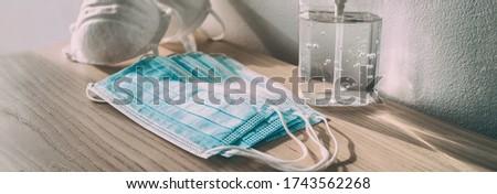 Coronavirus prevention medical surgical masks and hand sanitizer gel bottle dispenser for Covid-19 corona virus protection. Panoramic of PPE. #1743562268