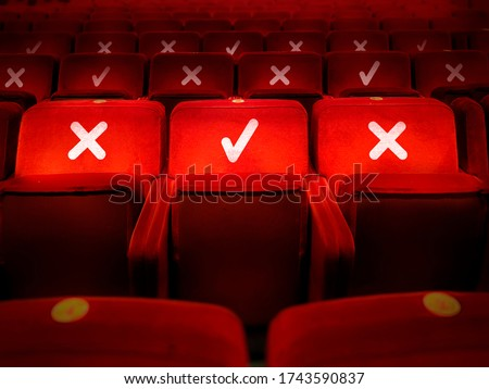 rows of empty chairs in a theater with the indication of where it is possible to sit to maintain the social safety distance during the period of the COVID-19 corona virus pandemic. Social distancing #1743590837