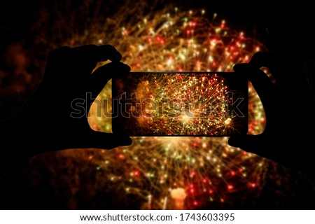 Taking the photo of fireworks via smartphone. Broadcast salute video to the internet