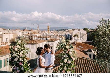 Interracial wedding couple. A wedding ceremony on the roof of the building, with cityscape views of the city and the Cathedral of Santa Maria Del Fiore. Destination fine-art wedding in Florence, Italy Royalty-Free Stock Photo #1743664307