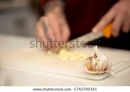 Clear picture of fresh garlic placing on white cutting board kitchen bench with defocused chef hand using sharp knife cutting chopping into small pieces at the background