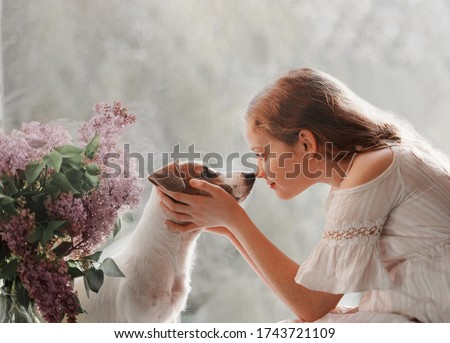 Cute little girl looks into the eyes of a dog. Two friends sitting on the window. Friendship, care, happy childhood concept. Royalty-Free Stock Photo #1743721109