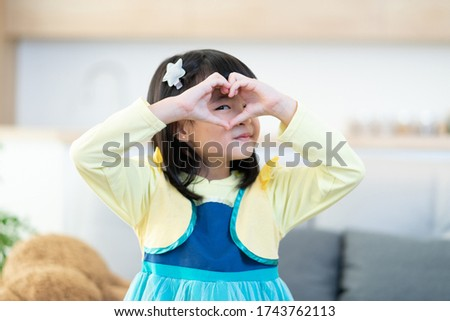 Portrait of Asian little girl kids wear cartoon princess cosplay clothing and show hand love symbol looking camera