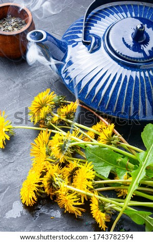 Ceramic teapot with herbal tea from flowering dandelions.Herbal tea from dandelions #1743782594