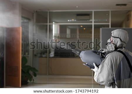 Sanitize office for covid 19 virus disease. Specialist in hazmat suit disinfecting coronavirus epidemic in office, prevention against Coronavirus disease 2019. Chemical spray at workstation area. Royalty-Free Stock Photo #1743794192