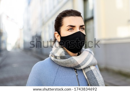 health, safety and pandemic concept - young woman wearing black face protective reusable barrier mask in city #1743834692