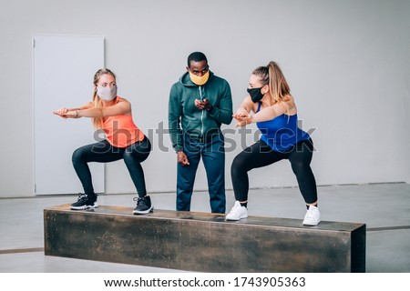 Two girls exercising with a personal trainer at the gym with protective mask in pandemic period of covid19 - Two fit young girls in a gym doing squats with their afro american trainer #1743905363
