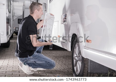 Caucasian Motorhomes RV Technician in His 40s Repair Travel Trailer Refrigerator From Outside. Recreational Vehicles Industry Theme. Royalty-Free Stock Photo #1743963773