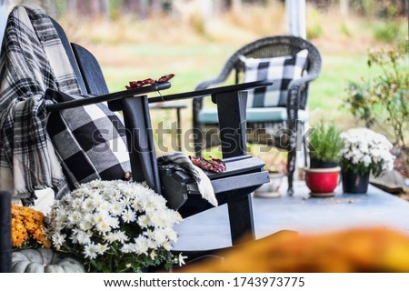 Adirondack rocking chair with style buffalo check blanket and pillows on a porch or patio decorated for autumn with heirloom gourds & white and orange mums. Selective focus with garden in background.