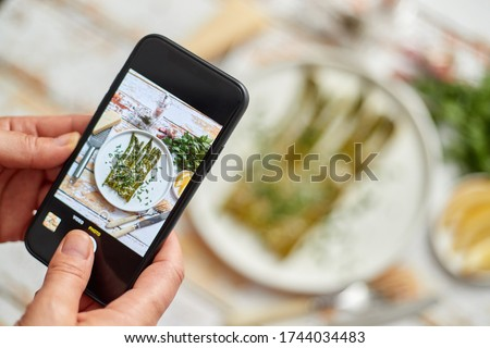 Woman taking picture of fresh prepared food with smartphone for social media. Roasted aparagus with herbs and parmesan.