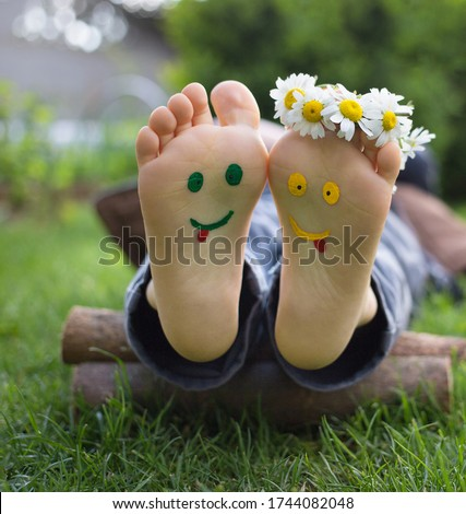 yellow and green faces are painted on the bare feet of a child lying on the grass. Chamomile flowers, green grass, joy, cheerful positive atmosphere, happy childhood. Hello summer, Smile Day Royalty-Free Stock Photo #1744082048