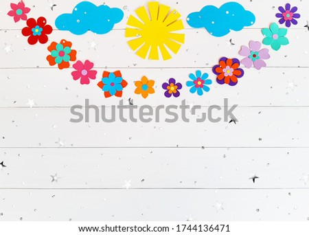 Composition of summer flowers, sun, clouds of multi-colored paper. Child make crafts his own hands. Cute DIY handmade art creativity on a white wooden table with stars, sequins. Top view, copy space