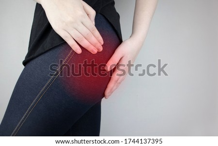 A woman suffers from pain in the buttock. The doctor diagnoses the patient piriformis syndrome, pinch of the sciatic nerve, lumbar osteochondrosis or sciatica Royalty-Free Stock Photo #1744137395