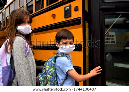 Boy and girl, students, children wearing face masks getting on school bus. For education, health, medical, environmental, and safety concepts regarding coronavirus, schools, reopening, and facemasks. #1744138487