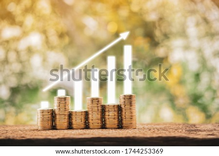 Arrow graph with growing value on stack gold coins put on the wood in the public park, Saving money for future investment plan concept. #1744253369