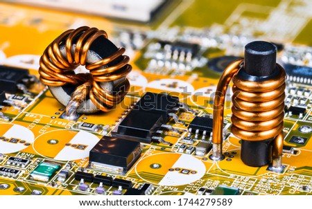 Toroidal and cylindrical inductor on circuit board of computer mainboard detail. Soldered induction coils with copper wire winding. Surface mount technology of micro chips, transistors and capacitors. #1744279589