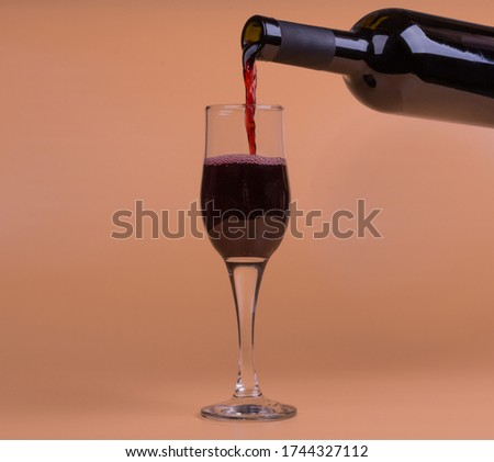 red wine is poured into a glass, photo on a beige background #1744327112