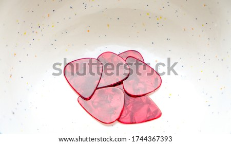 Red guitar pics in a speckled bowl