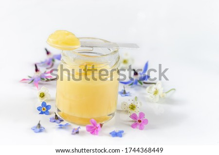 Raw organic royal jelly in a small bottle with litte spoon on small bottle on white Royalty-Free Stock Photo #1744368449