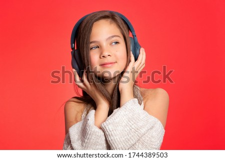 Girl in the headphones. Lovely European girl teenager 10 years old listens to music on headphones, relaxes, enjoys. Music lover since childhood. Music fan, DJ. Portrait on a red background.