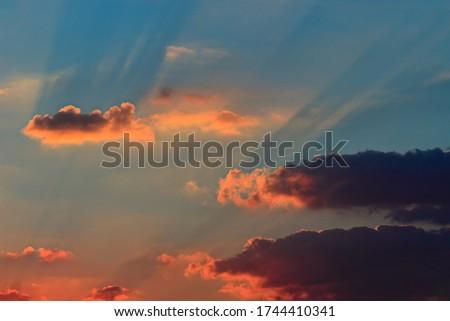 twilight rays between orange shaded clouds during twilight - POA, SAO PAULO, BRAZIL.