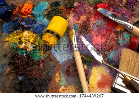 paintbrushes with multicolored paints on a brown floor #1744439267
