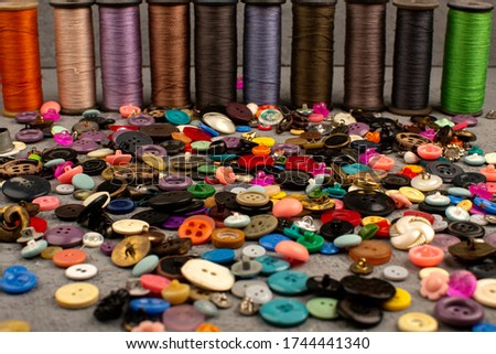plastic buttons sewing multicolored along with colorful sewing threads on a grey desk #1744441340