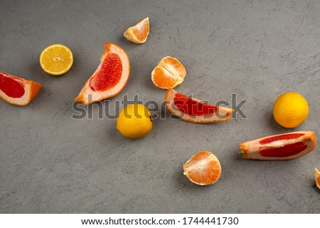 sliced citrus fruits like grapefruits lemons and tangerines on the grey background #1744441730