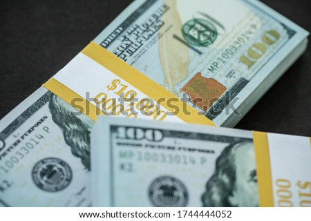 Two bundles of cash money, $10,000 each, stacked on a black background. (Prop money, fakes for motion picture use.)