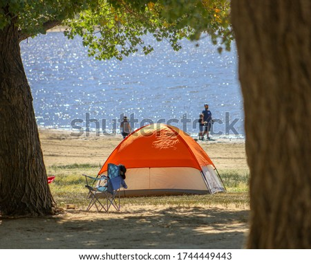 A tent by the lake and family on the background.