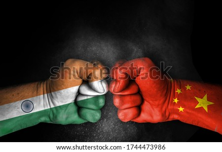 Conflict and tension between India and China, male fists with flags painted on skin isolated on black background - fight and conflict between two countries concept #1744473986