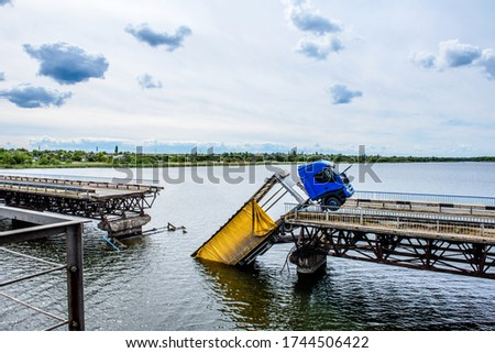 Destruction of bridge structures across the river with the collapse of sections into the water. Truck accident on destroyed bridge Royalty-Free Stock Photo #1744506422