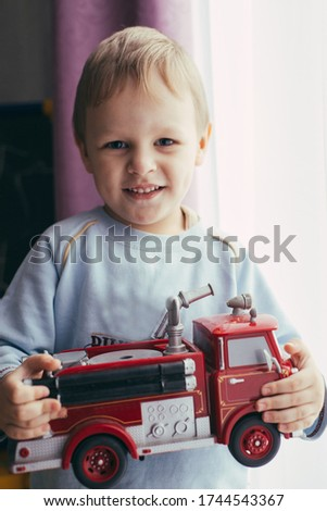 Little boy playing with fire truck