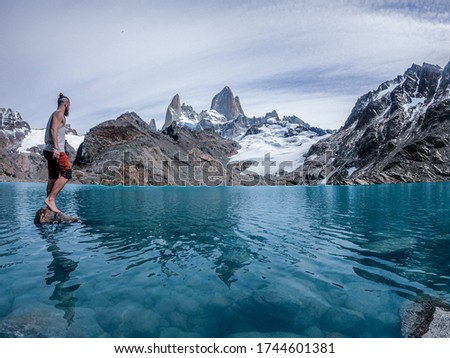 Nordic man on stone in glacier lake patagonia argentina with fitz roy mountain in the background