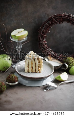 Slice of vertical biscuit cake with apple filling on a plate. Autumn desserts.  Royalty-Free Stock Photo #1744615787