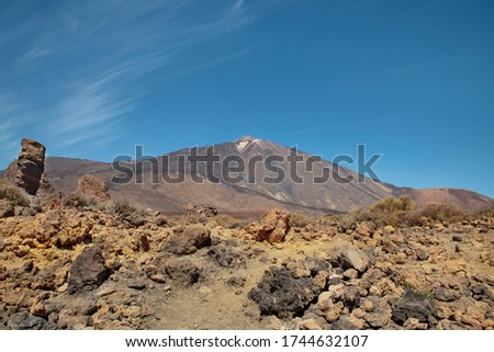 Mount Teide surrounded by the rocky volcanic and unusual landscape with Roque Cinchado on the left situated in the popular travel destination Teide National Park, in Tenerife, Canary Islands, Spain #1744632107