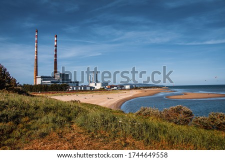 Irish coastline in summer with a view of Poolbeg Towers and  beach.he thermal station chimneys are among the tallest structures in Ireland and are visible from most of Dublin city #1744649558