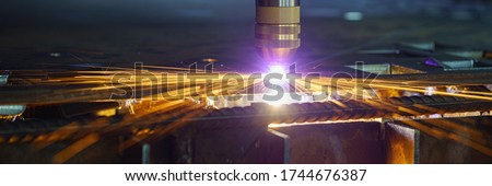 Plasma cutting machine cuts metal material with sparks Royalty-Free Stock Photo #1744676387