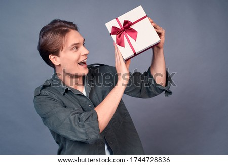 Image of a happy young funny guy who receives birthday presents, shakes with a wrapped box, trying to guess what is inside, screaming as excited and excited as opening presents, gray background.