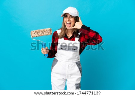 Painter woman over isolated blue background making phone gesture. Call me back sign